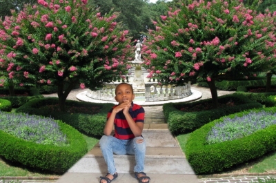 Boy sitting on stairs with beautiful flower background