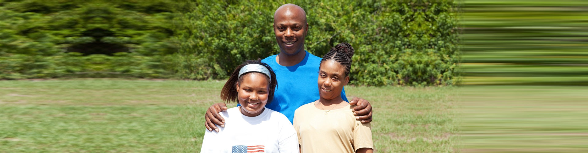 adult man and two female kids smiling